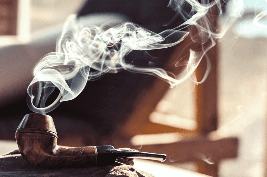 dymiaca fajka na tabak polozena na kuse dreva vo svetle zapadajuceho slnka