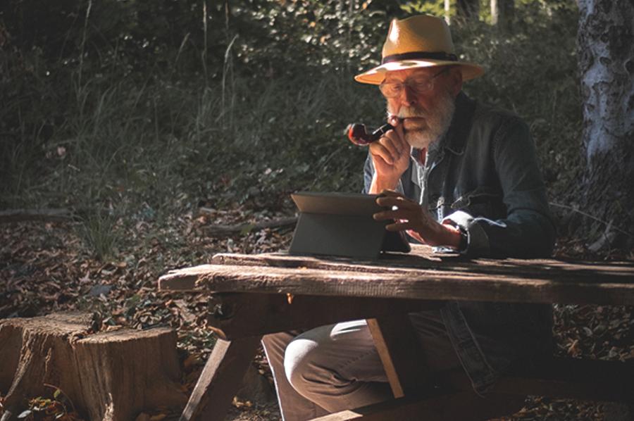starsi pan sedi v lese za stolom pricom fajci tabak cez fajku a cita si knihu