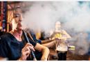 žena fajčí vodnú fajku v bare a vyfukuje hustý dym