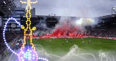 futbalový štadión svetlice neónové značenie vodná fajka dym fanúšikovia štadión