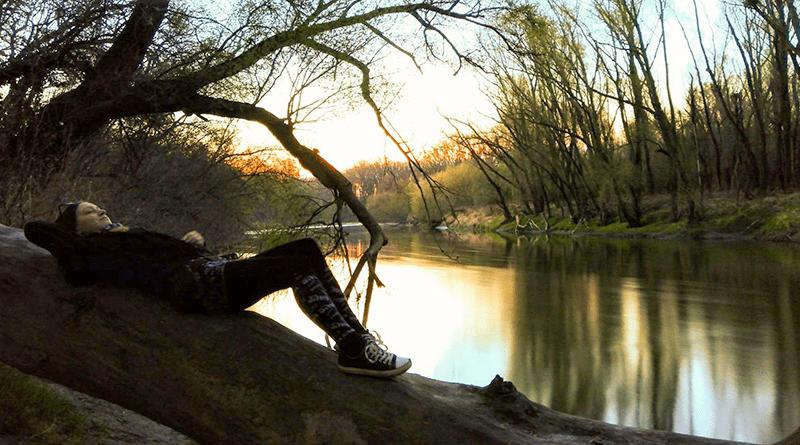 žena leží a relaxuje na stome pri vode a v ruke drží fajku
