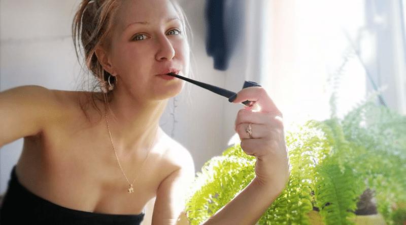 žena fajčí fajku na tabak pri okne a papradí