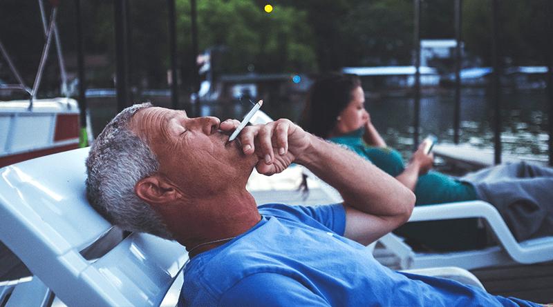 muž fajčí cigaretu zatiaľ čo je pokojný a leží
