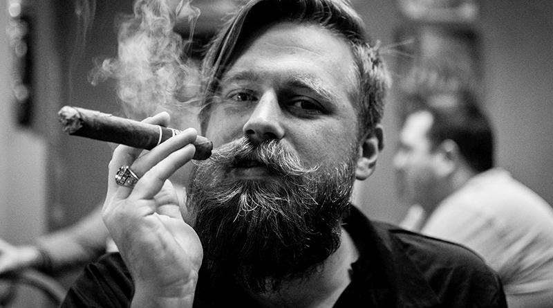 mladý muž má upravenú bradu a fajčí cigaru