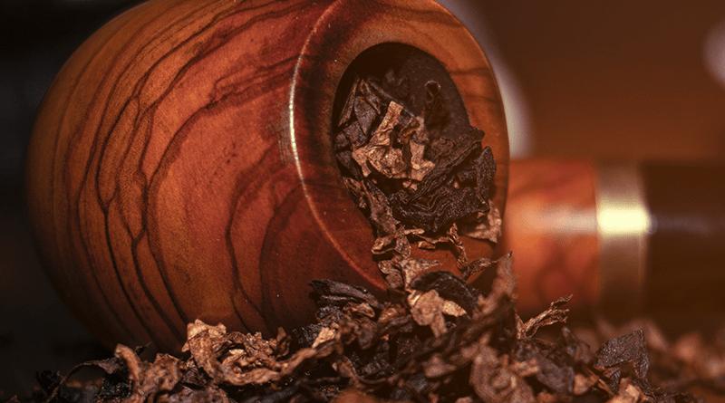 Fajka na tabak leží a z jej hlavičky sa sype tabak