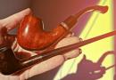 ženská ruka držiaca fajku na tabak a fajku na čítanie