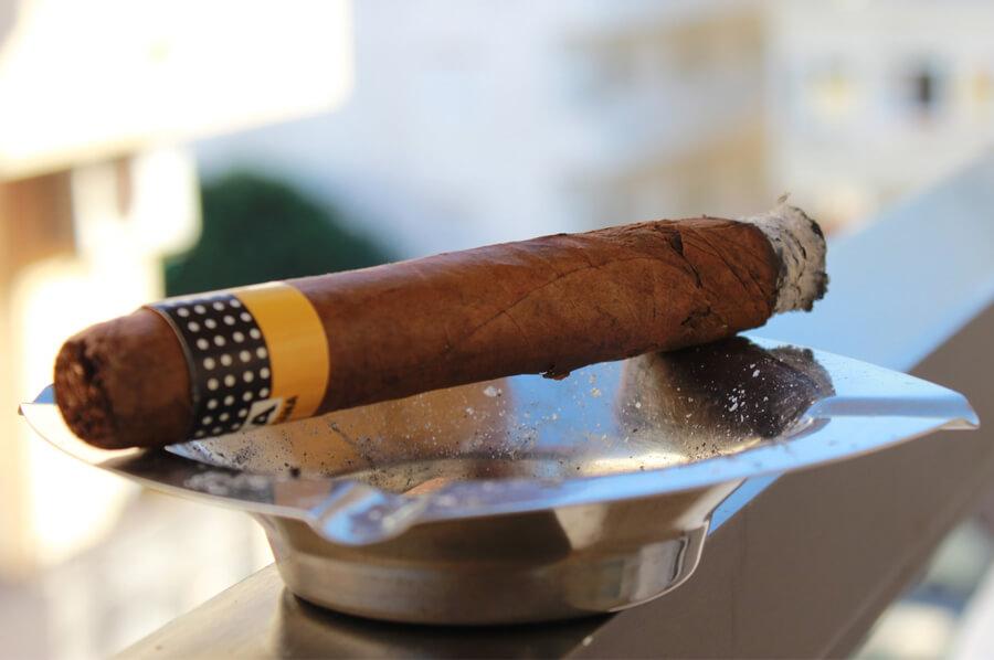Cigara značky Cohiba položená na popolníku