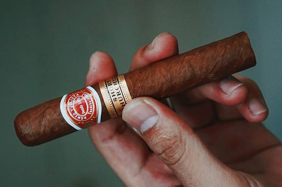 Cigara Romeo y julieta Short Churchill v mužskej ruke