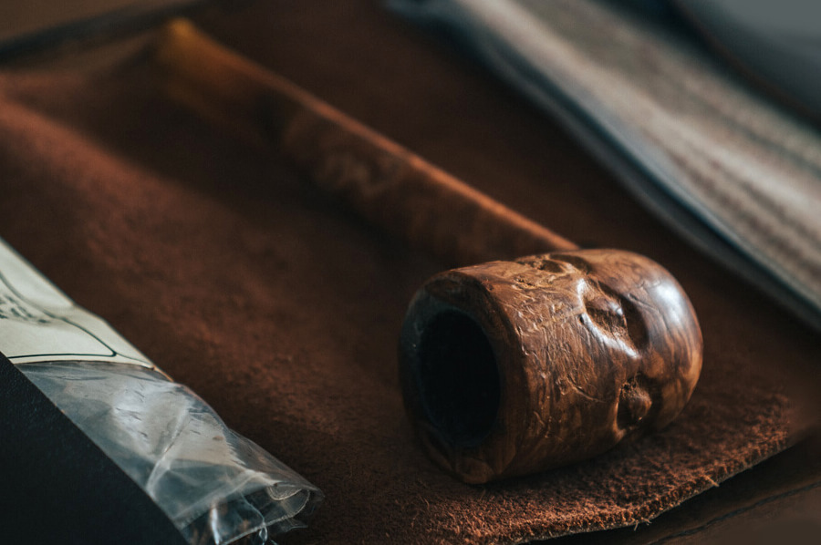 Drevená fajka so známkami používania položená na koženom púzdre