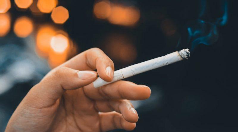 Ruka, ktorá drží zapálenú cigaretu