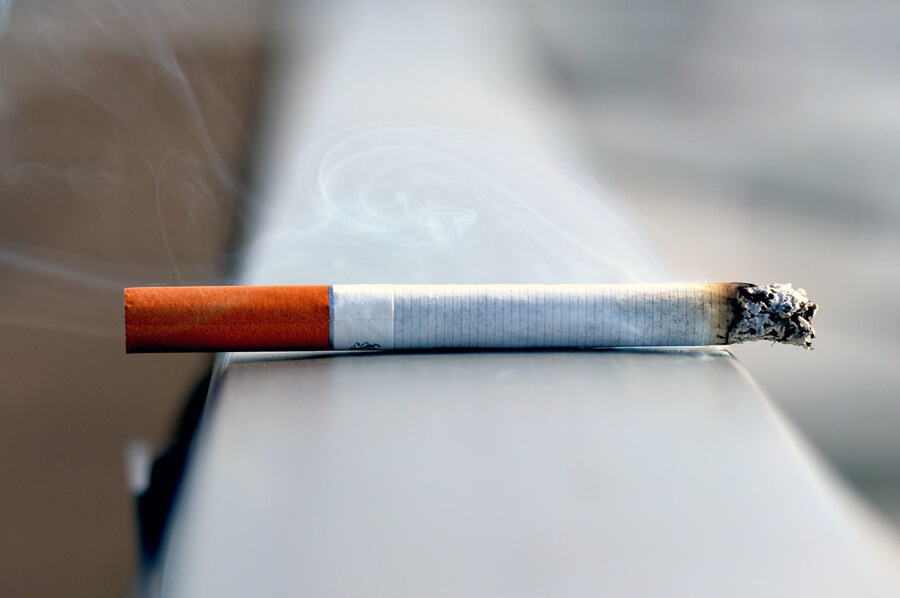 Zapálená cigareta odložená na zábradlí