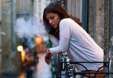 Žena fajčí na malom balkóne, pod ňou je rušná ulica