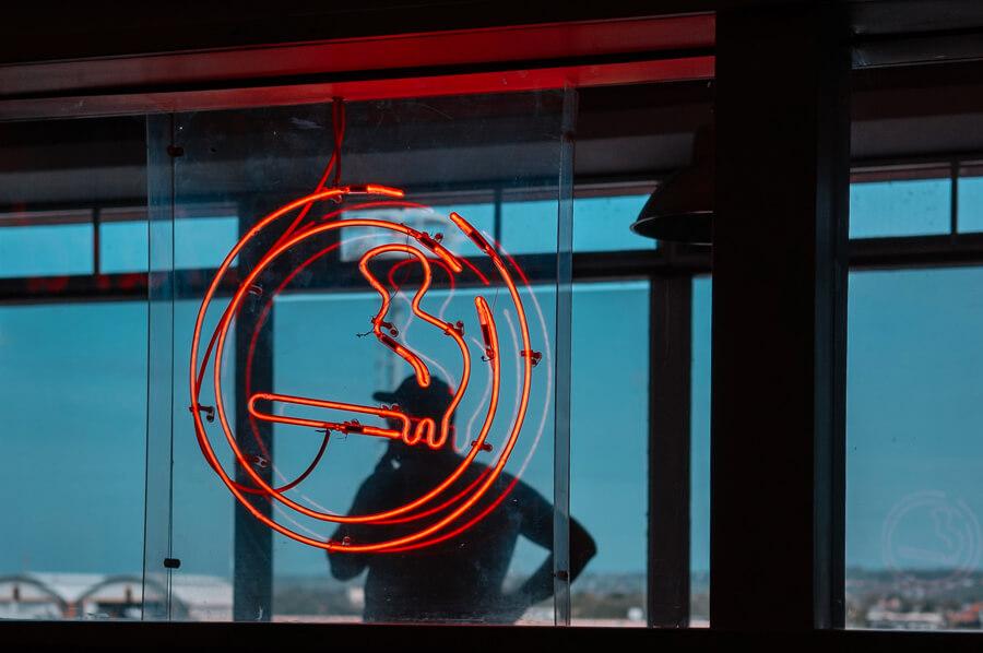 Neónový znak s cigaretou, na pozadí fajčí muž