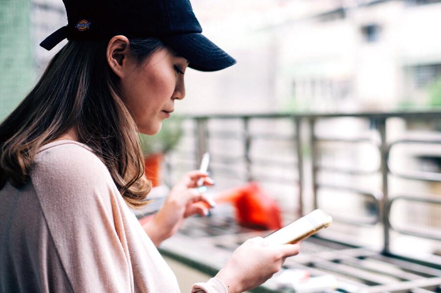 Žena v šiltovke fajčí cigaretu na balkóne a sleduje svoj smartfón