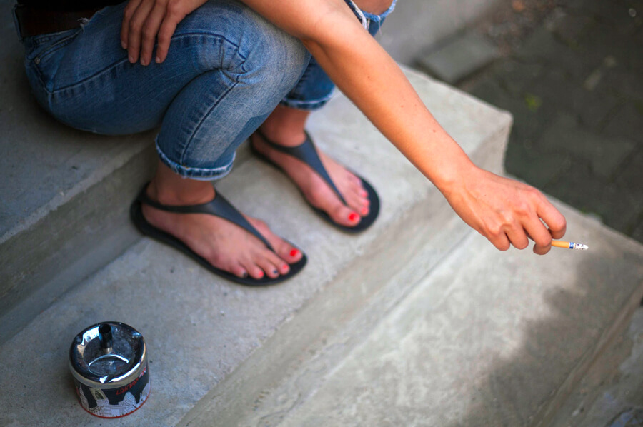 Fajčenie na schodoch - mladá žena fajčí cigaretu na schodoch