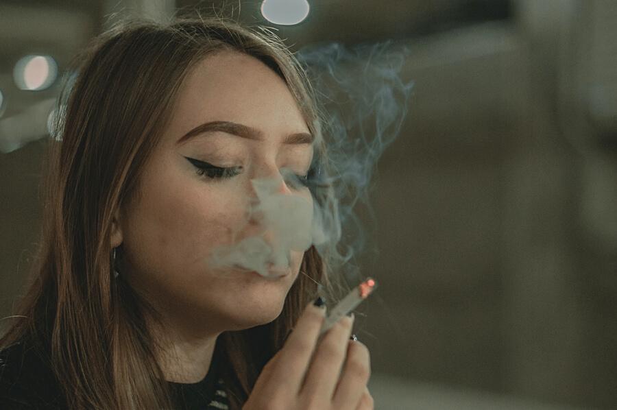 Mladá žena fajčí cigaretu, vydychuje dym