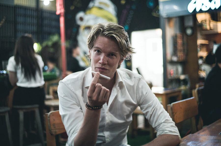 Mladý muž sedí za barom a v ruke drží nezapálenú cigaretu