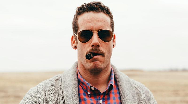 muž s cigarou v ústach má tunely v ušiach a letecké okuliare ray ban