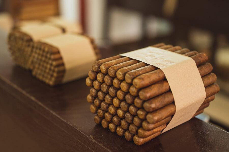 Veľké balenie cigár zabalené papierom na drevenom pulte